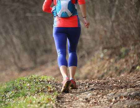 Woman runs fast with the sport suit in the mountain trail during the race photographed from behind