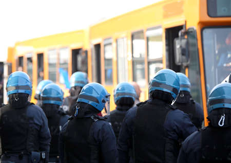 riot police with protective helmet escort the buses of fans to the stadium 版權商用圖片