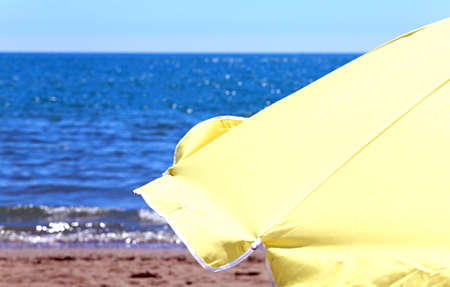 luxuriously: Large yellow parasol on the shore of the ocean in the hot summer sunny day Stock Photo