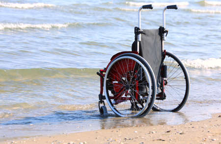Wheelchair on the shore by the sea on a hot sunny day