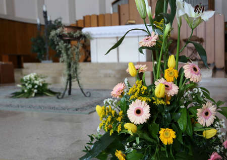 baptismal: gerberas flowers and calla lilies at the baptismal celebration inside a church Stock Photo