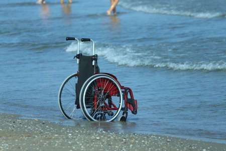 Wheelchair on the shore by the sea on a hot sunny summer day Stock Photo