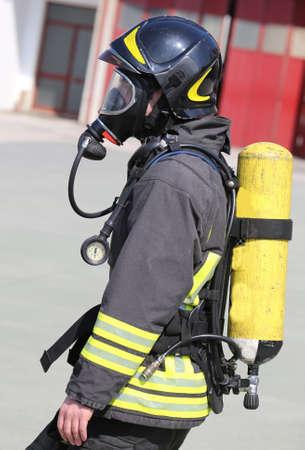 Pompier avec grande bouteille d'oxygène jaune et respirateur automatique