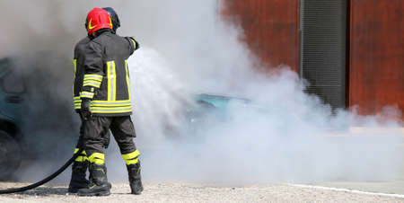firefighters with uniform and protective helmet extinguish the fire of the incident car during a firefighting exercise