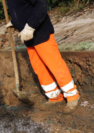 man at work in the trench in the roadwork with the shovel Stock Photo