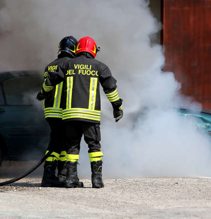 extinguishing: Two Italian fire brigade with the letter on the uniform meaning firemen turn off the fire of the car during an anti-fire exercise