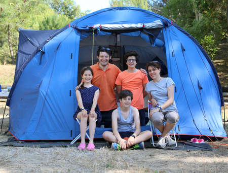 Five-person family with three smiling children and tent in summer camping