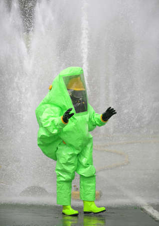 Man with a green protective suit against radiation and chemical agents and polluted air and water on background