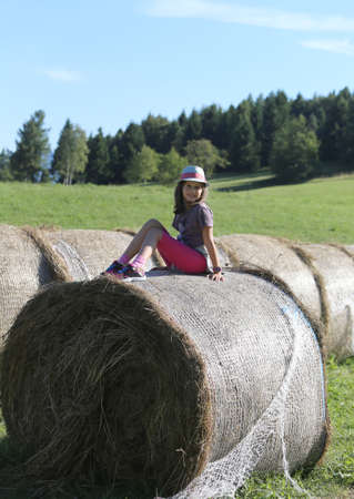 outer clothing: Pretty little girl with long brown hair over hay bale in the countryside Stock Photo