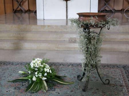 Antico Piccolo fonte battesimale in rame decorato con fiori durante la celebrazione religiosa all'interno della chiesa