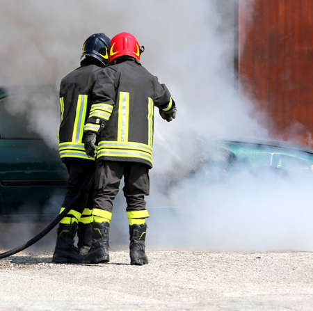 Two firefighters with uniform and protective helmet extinguish the fire of the incident car during a firefighting exercise