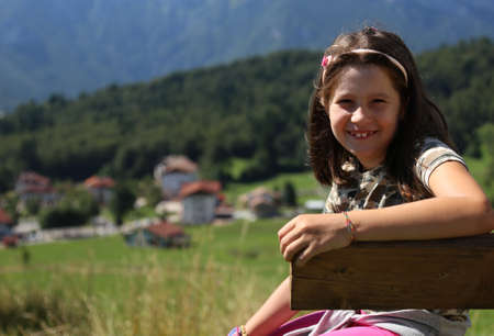 Nice caucasian little girl with long brown hair smiling on bench in mountain in summer