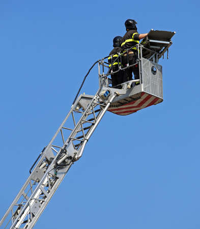 Two intrepid firefighters over the ladder truck metal basket during the recovery of a wounded