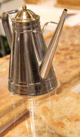 Modern steel oil cruet in a Neapolitan pizzeria to season the pizza