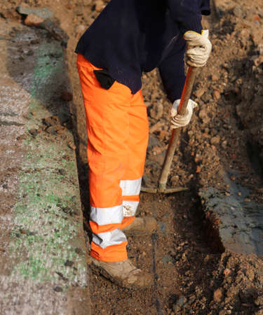 worker with the orange pants in the trench inside a construction site Stock Photo