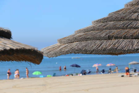 Large straw beach umbrella to shelter from the hot summer sun by the sea with many people in the ocean