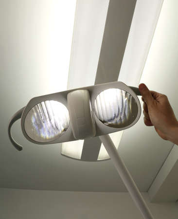 subjective: Powerful light in the medical facility and the hand of a surgeon who directs the spotlight to the patient