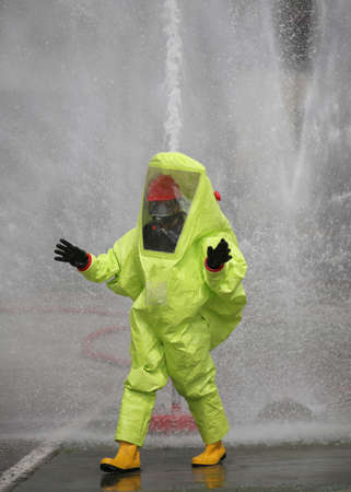 Man with yellow protective suit against radiation and chemical agents and splashes of water in the background Stock Photo