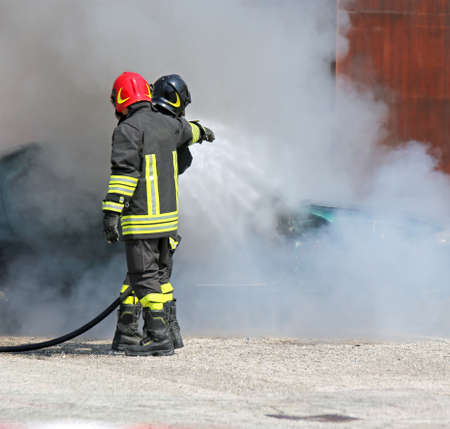 Two firefighters with uniform and protective helmet extinguish the fire of the incident car