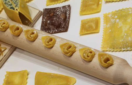 raviolo: Fresh italian pasta of many sizes with wooden rolling pin and tortellini and ravioli in the restaurant