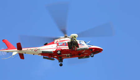 fireman: Veneto, Italy - May 26, 2016: Italian helicopter  of fire department while flying during an exercise to recover injured people after accident