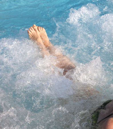 Woman in spa pool and whirlpool at her feet with nails with golden enamel