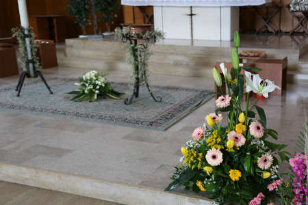 Baptismal celebration inside a Christian church with flowers and altar Stock Photo