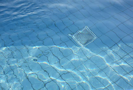 Background with clear pool water and metal grill for recirculation and purification