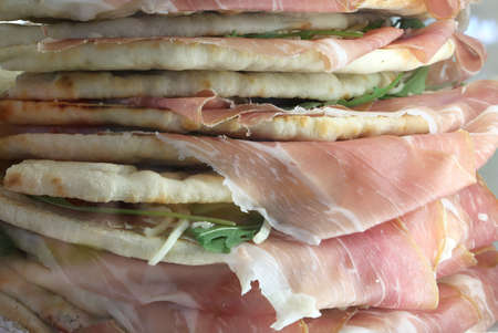 sandwiches called Spianata or Piadina in Italian with raw ham and arugula Imagens