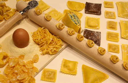 tortellini: Fresh pasta of many sizes with wooden rolling pin and tortellini and ravioli