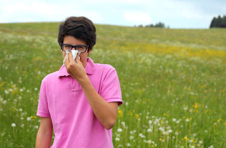 Allergic boy with glasses and pink t-shirt blows his nose using a handkerchief in middle of a field
