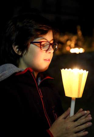 eucharistie: Jeune garçon caucasien avec bougie lors d'une masse de relgion en plein air