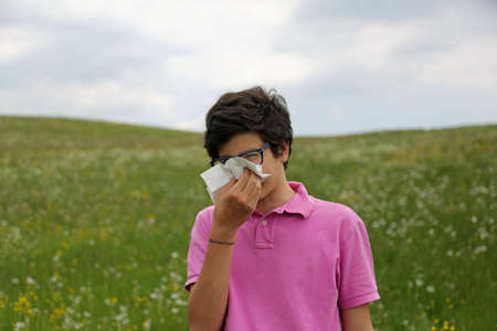 Allergic boy with pink t-shirt blows his nose with a white handkerchief