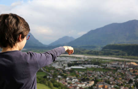 young boy pointing to the underlying panorama of  the valley with town and river