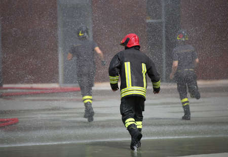 Firefighters run under the splashes of water during fire extinguishing
