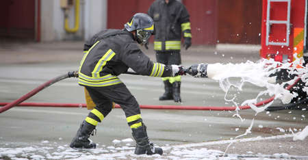 Firefighters while extinguishing the fire with a special fire extinguishing equipment with foma Stock Photo