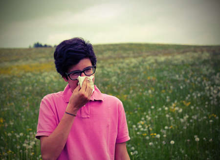 hankie: young boy wuith allergy blows his nose in springtime Stock Photo