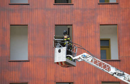 bucket truck with firefighters during exercise in the firehouse and the building for the practical tests Stock Photo - 82136622