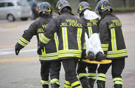Italian firefighter team uniform with firefighters writing while helping the wounded after a tragic road accident