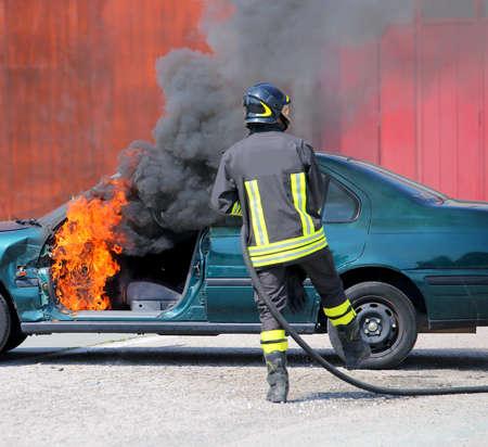 gebroken auto met vlammen en zwarte rook en brandweerman ingrijpen om te knoeien met het vuur