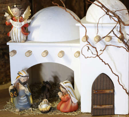 Palestinian nativity scene with holy family set in the middle east with a typical white house and an Angel whit text GLORIA that means GLORY in Italian