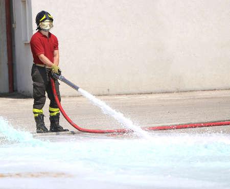 De brandweerman met de hydrantgeest test de stroom van water tijdens oefening in de brandweerkazerne