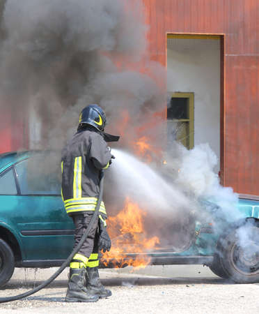 broken car with flames and black smoke and firefighter intervening to tamper with the fire Editorial