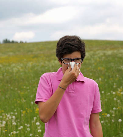 hanky: Allergic boy with glasses and pink t-shirt blows his nose using a white handkerchief in springtime
