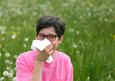 Allergic Child with glasses blows his nose in the middle of the meadow with dandelion Stock Photo