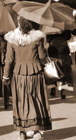 ladies dressed in vintage clothes and a umbrella with sepia effect