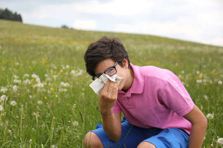 Allergic boy with glasses blows his nose using a white handkerchief in springtime Stock Photo