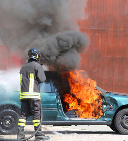 fireman: broken car with flames and black smoke and firefighter intervening to tamper with the fire Stock Photo