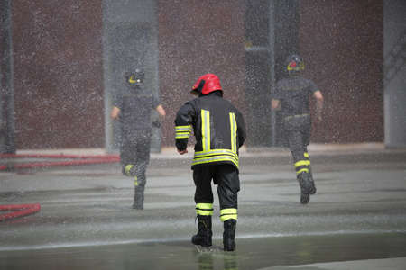 fireman: Firefighters run fast under the splashes of water during fire extinguishing Stock Photo