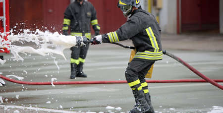 fireman: Firefighters while extinguishing the fire with a special fire extinguishing equipment with foma Stock Photo